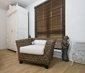 interior detail with vintage wardrobe and rattan armchair