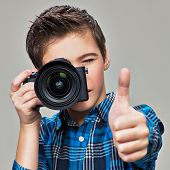 Boy with photo camera taking pictures. Teenager  boy  with photo camera shows the thumb up poster
