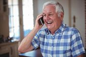 Cheerful senior man talking on mobile phone at home poster