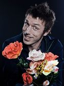 studio portrait on black background of a funny expressive caucasian man offering flowers cheerful se