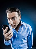 caucasian man staring cellphone portrait isolated studio on black background