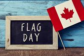 a wooden-framed chalkboard with the text Flag Day written in it and the flag of Canada placed on a r poster