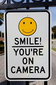 A Smile You're on Camera sign affixed to security gates