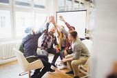 Happy creative business people giving high-five in meeting room at creative office poster