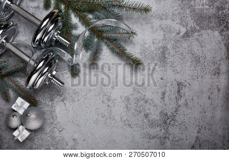 poster of Dumbbell, fir tree branches, gifts and Christmas decorations  on a gray background. New Year and Chr