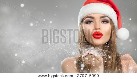504b601bc4c1a Christmas Winter Fashion Girl blowing snow in Her Hand. Beautiful New Year  and Xmas Holiday Makeup. Gift. Beauty Model woman in Santa hat on Holiday  Blurred ...