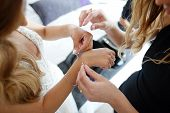Bridesmaid Helps To Put A Bracelet On His Arm For The Bride. Bride Putting On Jewelry, Focus On Brac poster