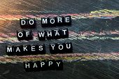 Do More Of What Makes You Happy On Wooden Blocks. Cross Processed Image With Blackboard Background.  poster