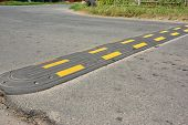 Traffic Safety Speed Bump On An Asphalt Road. Speed Bumps Or Speed Breakers Are Traffic Calming Devi poster