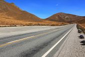 Long road stretching out to  dry mountain range at Lindis Pass, the highest highway, in New Zealand