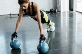 Focused Fit Sportswoman In Weightlifting Gloves Doing Plank Exercise On Kettlebells At Gym poster