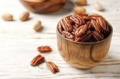 Tasty Pecan Nuts In Dish On Wooden Table. Space For Text poster