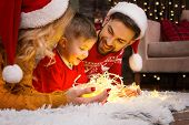Family In Santa Hats With Child Kid Boy Playing With Light Christmas Garland In Warm Red Sweaters Ly poster