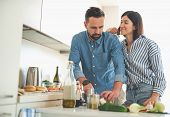 Beautiful Young Lady Gazing At Boyfriend While He Cooking Dinner poster