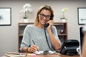 Beautiful mature woman talking on phone at creative office. Happy smiling businesswoman answering te poster