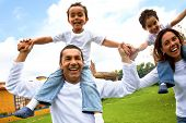 stock photo of happy family  - happy family smiling and having fun outdoors - JPG