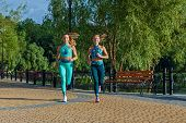 Girls In Sports Rompers Warm Up And Run. Fitness On The Street. Attractive Girls Doing Exercises On  poster
