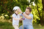 Middle Age Father Helping His Little Son To Put His Helmet. Active Family Leisure With Children. Saf poster
