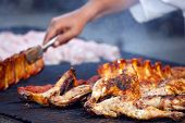 barbecue of grilled chicken legs with chef's hands