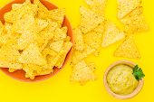 Snack For Party. Mexican Nachos Near Guacamole Sause On Yellow Background Top View poster