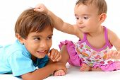 stock photo of pulling hair  - Young sister pulling hair of his brother  - JPG