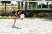 Teenage girl playing volleyball on a sand court poster