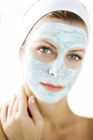 stock photo of face mask  - young woman wearing a skin mask looking at camera - JPG