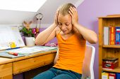 Familia - niño en casa sentado en su escritorio y hacer la tarea y no tiene mucha diversión