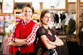Traditional clothes - young couple is buying Tracht - a dirndl and a lederhosen in a shop, they do try it on before