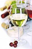 Uva e queijo com uma garrafas e copos de vinho tinto e branco