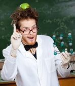 Mad scientist with a green apple on his head shows forefinger while handing molecular	model