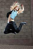Teenage girl dancing hip-hop over the street wall