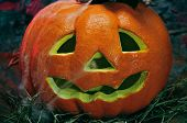 closeup of a Halloween jack-o-lantern in a dismal scenery