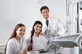 Portrait of happy young dentist and nurse with patient in clinic