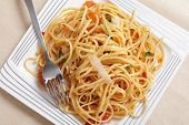 Linguine pasta tossed in a sauce of olive oil, tomato, garlic and basil and topped with slivers of p