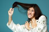 Funny teen girl try to bomb her hair in the morning. Over blue background.