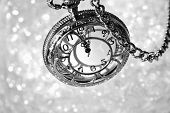 Silver vintage pocket watch with chain as viewed from above over bokeh background.  Side lighting wi