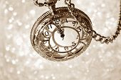 Vintage pocket watch with chain as viewed from above over bokeh background.  Side lighting with shad