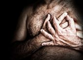 image of breast-stroke  - Gritty image of a shirtless man suffering from chest pain and grabbing his chest - JPG