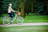 Female biker in a park, intentional motion blur (panning)