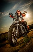 stock photo of rebel  - Biker girl with sunglasses sitting on motorcycle - JPG