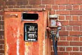 stock photo of bowser  - dilapidated red petrol pump against a brick wall - JPG