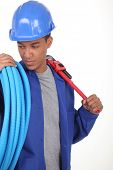 Young worker with blue flexible tube and a wrench