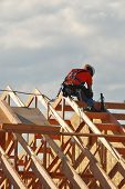picture of rafters  - A worker tying in the final roof rafters on a new bank building in Roseburg Oregon - JPG