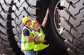 shipping company workers checking industrial tires before exporting