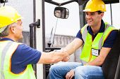 two warehouse forklift drivers handshaking when shift change over
