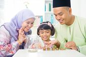 Islamic banking concept. Southeast Asian family counting money at home. Little Malay girl and parent