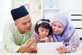 Southeast Asian family using tablet pc computer online shopping with credit card at home. Muslim family living lifestyle. Happy smiling Malay parents and child.