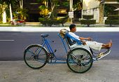 Nha Trang, Vietnam, March 2013: an unidentified man - rickshaw waiting for a client on a city street