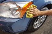 stock photo of auto garage  - Hand polishing car fender with yellow cloth - JPG